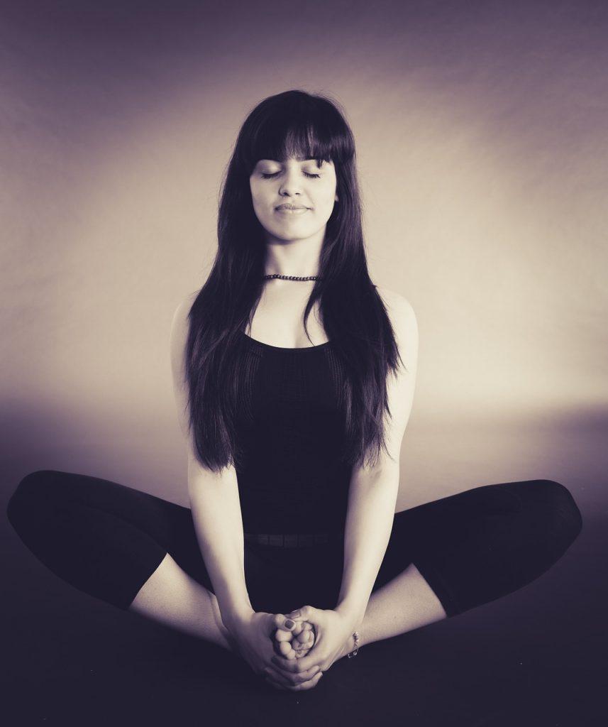 a pretty girl meditating doing yoga
