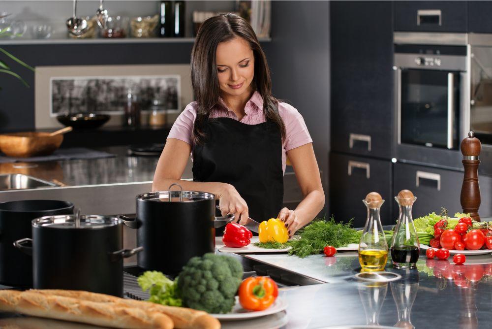 Cheerful woman chopping veggies in the kichen