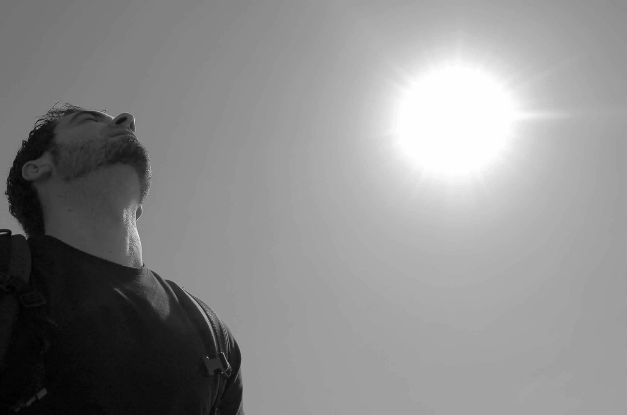 man breathing under the sun and sky