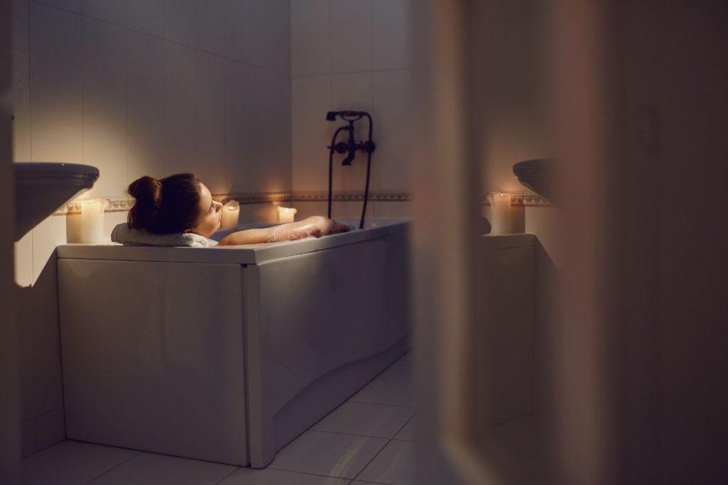 Woman in a bathtub in a cozy serene candlelit bathroom