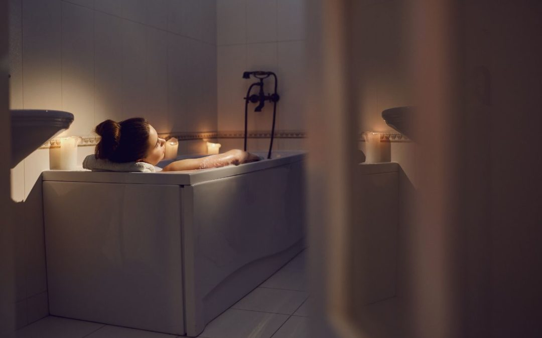 Woman in a bathtub in a cozy serene candlelit bathroom