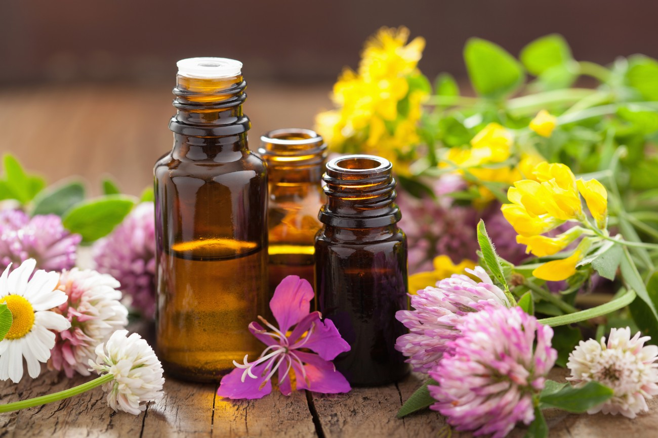 Essential oils surrounded by flowers and herbs