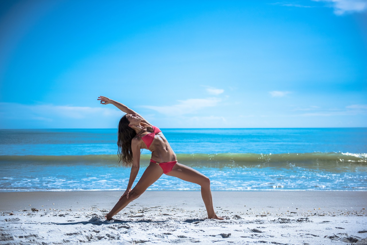 A woman stretching and doing yoga by the beach