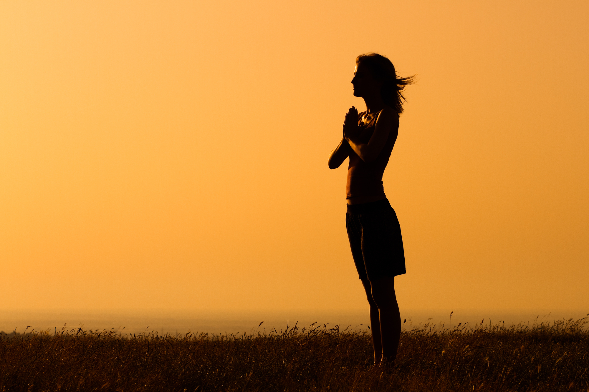 Woman in a thankful prayer pose out in nature during sunset