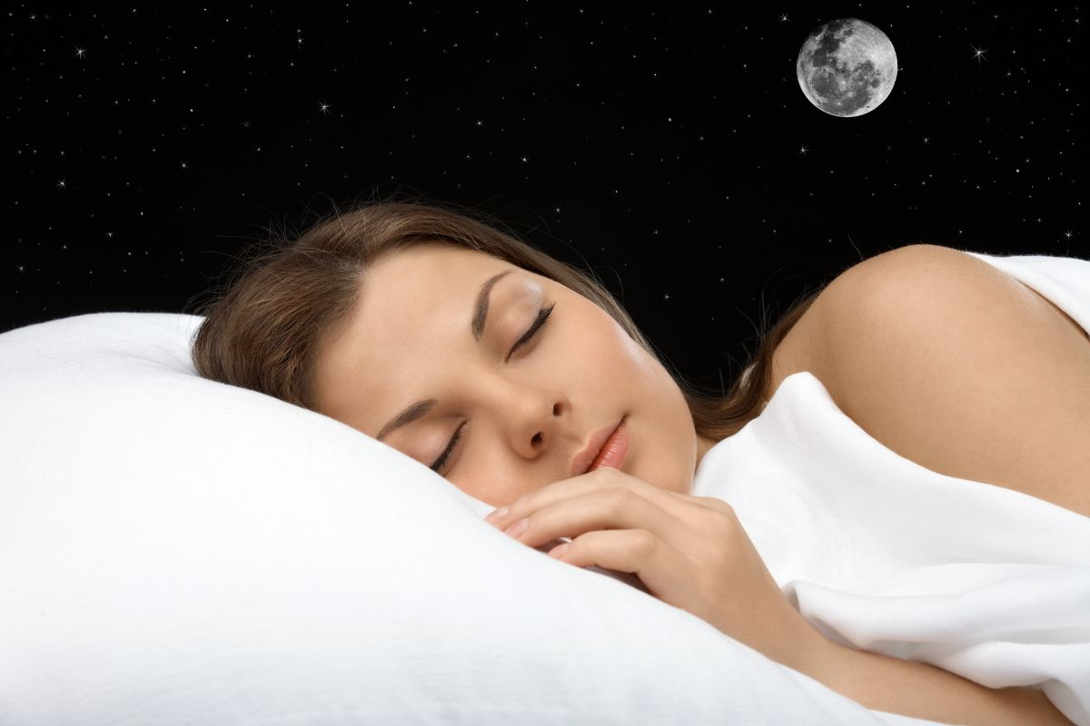 Young woman sleeping, moon and stars in the background