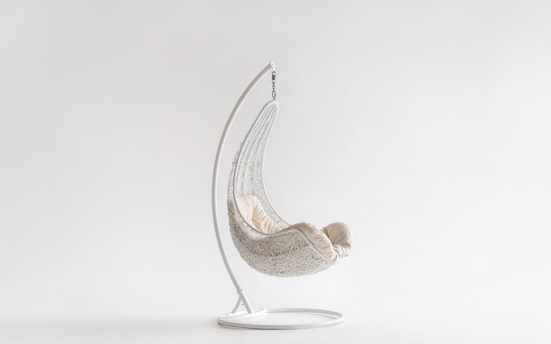 Hanging wicker white armchair/podchair with a beige pillow on the light background in the studio. It is hanging on the metal holder with a round support.