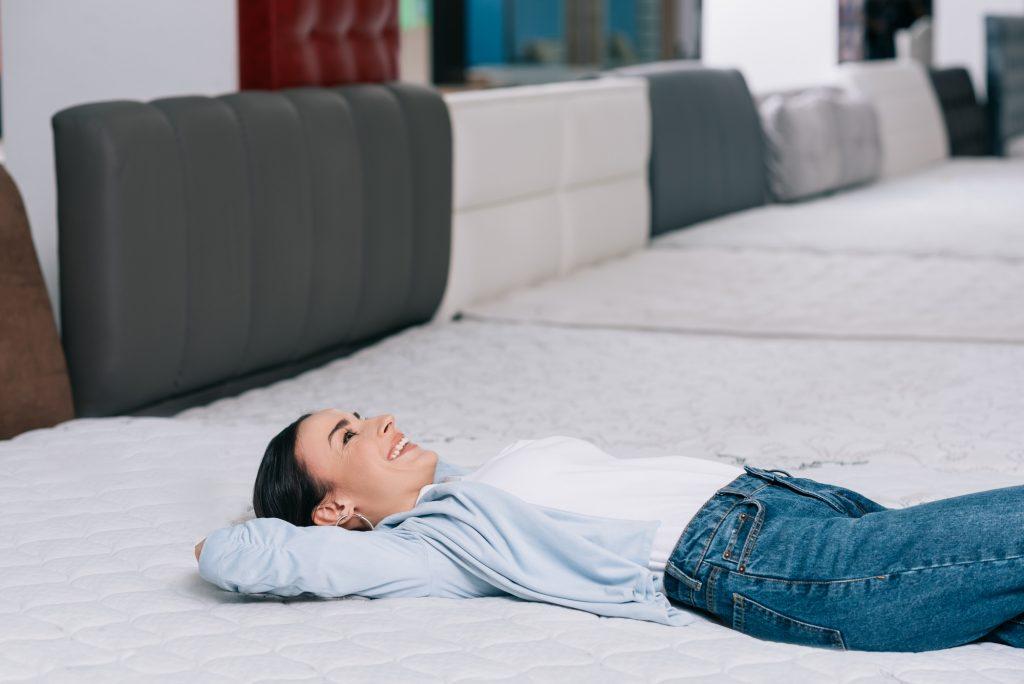 Woman testing mattress while smiling