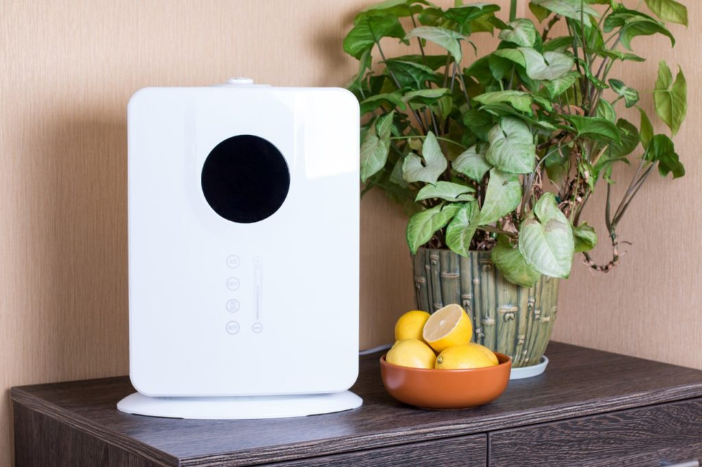 Air purifier surrounded by lemons and green plant