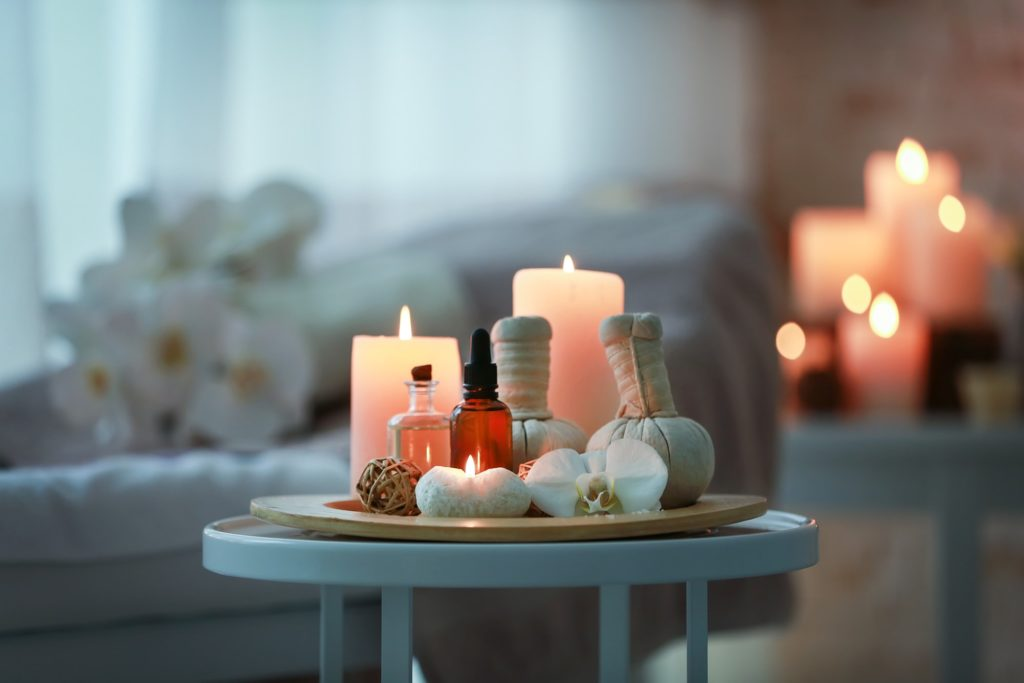 Essential oils on a small table with candles on