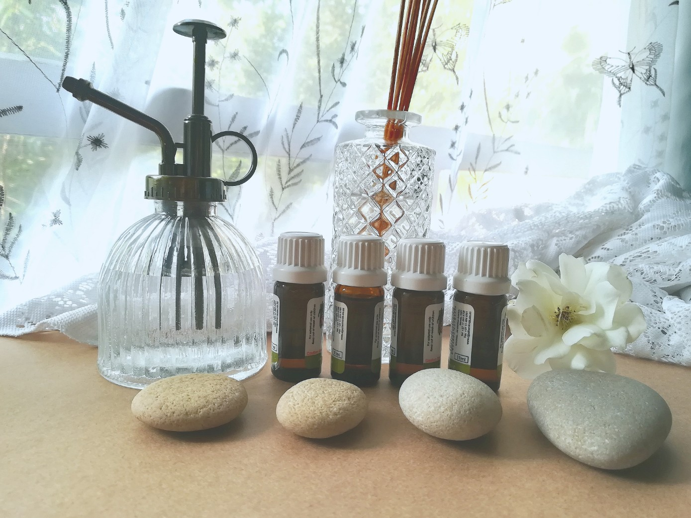 Essential oils and diffuser with meditative stones and sticks