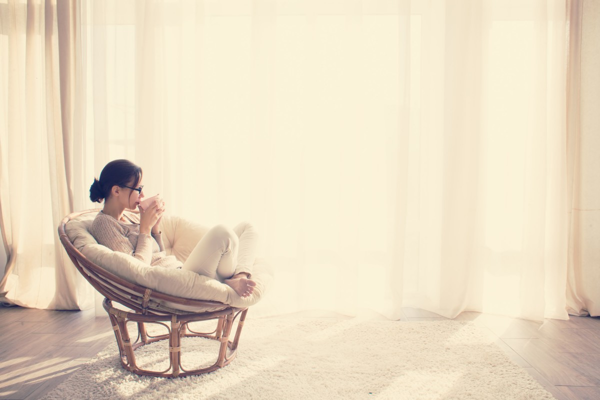 Woman drinking tea / coffee in a bright cozy room