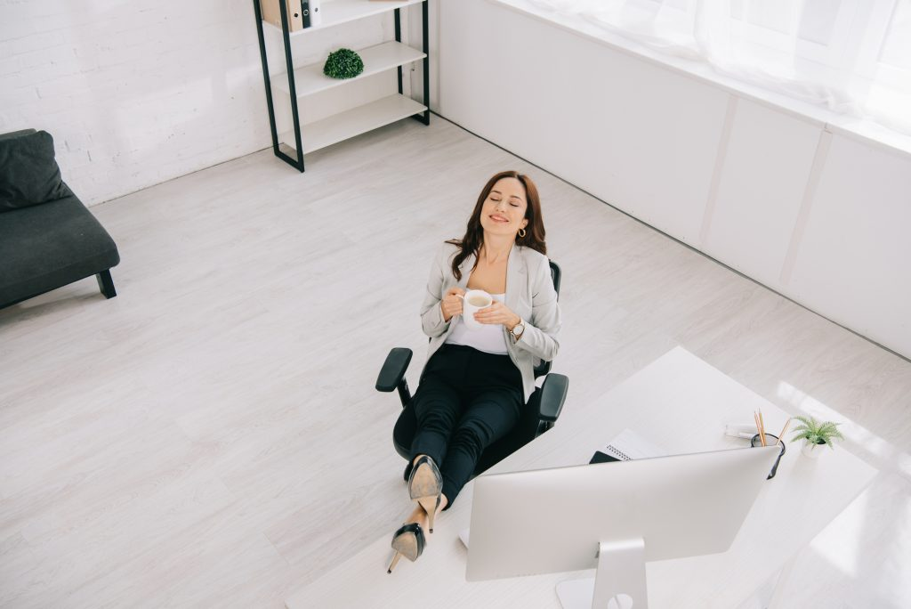 Young woman taking coffee break from computer