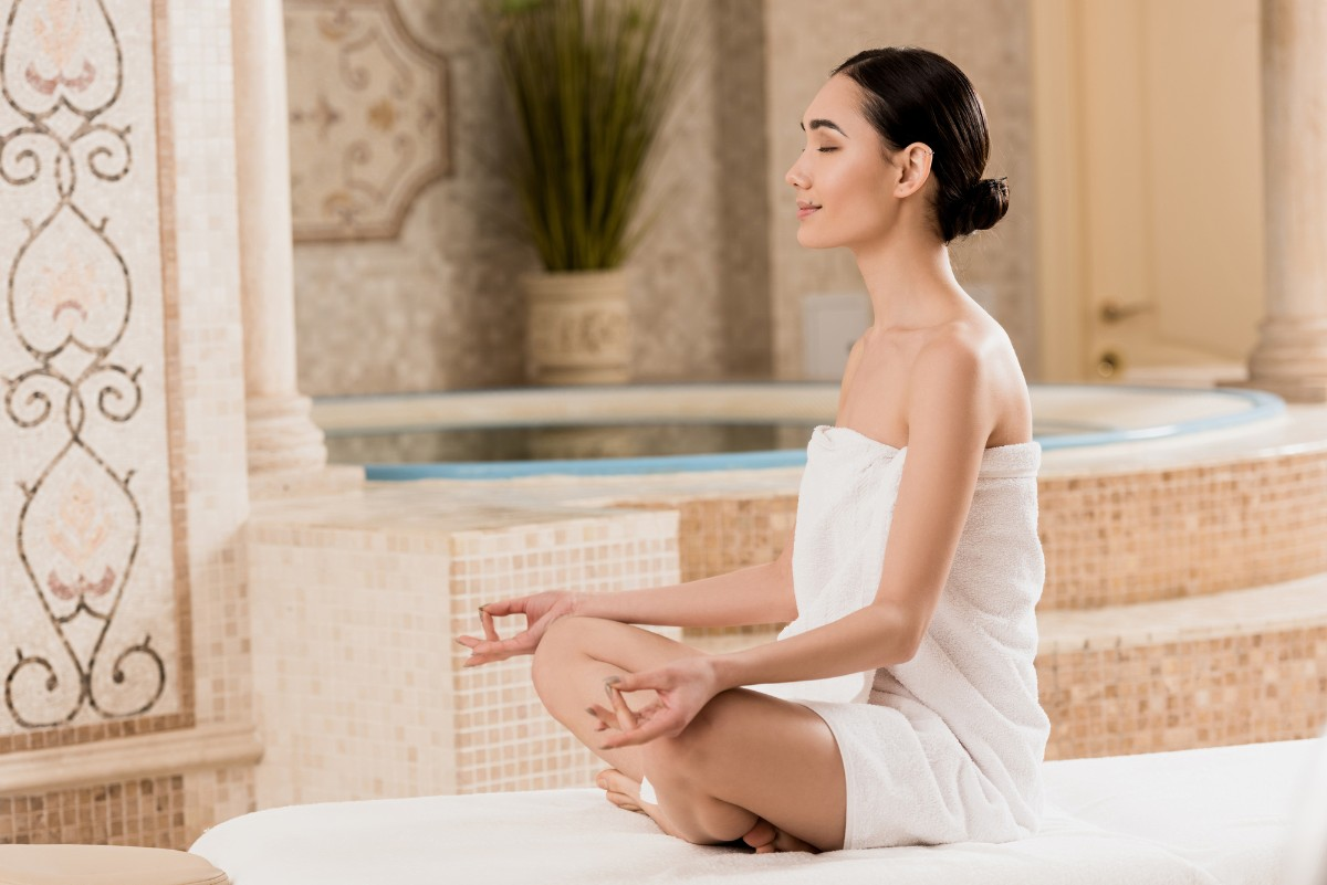 Asian woman meditating in a luxury spa