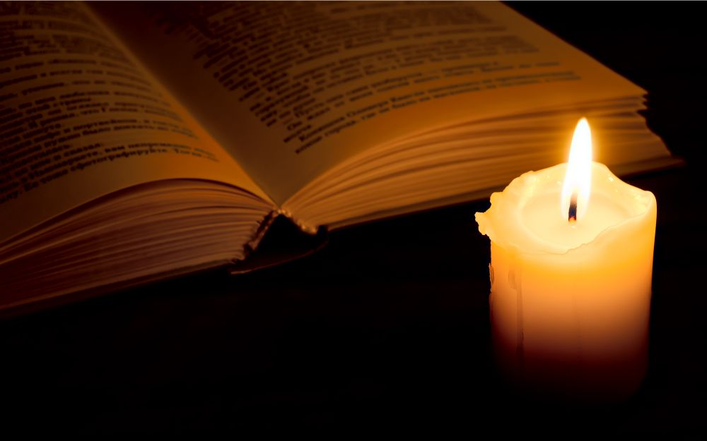 Candle light by a book