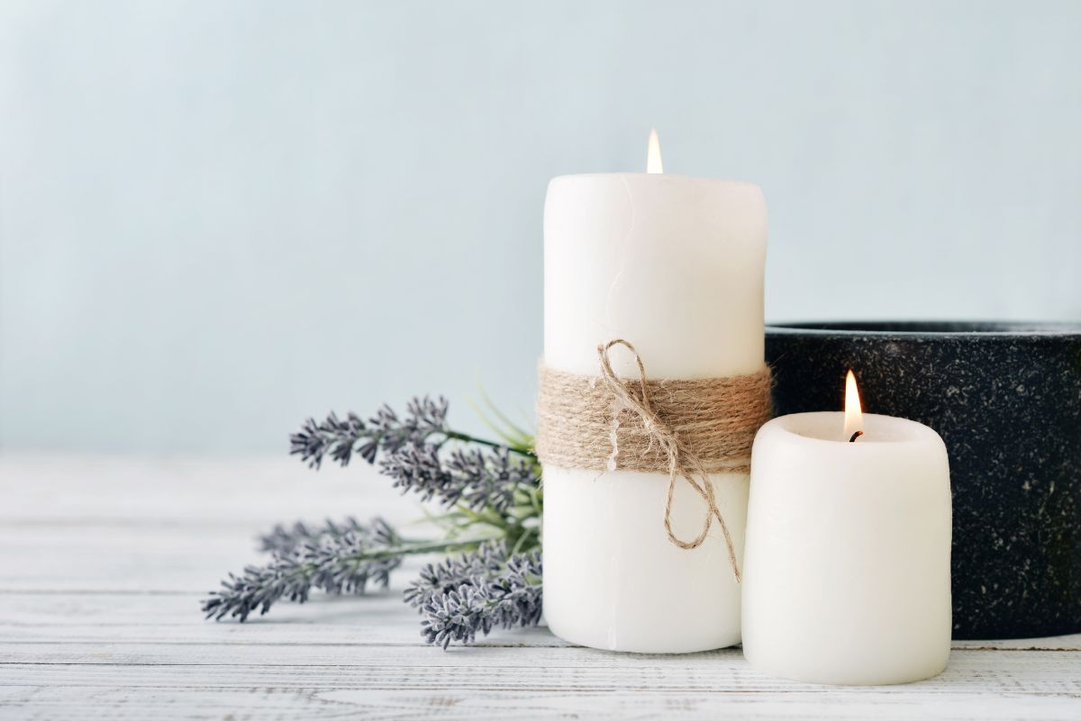 Two candles beside a lavender flower