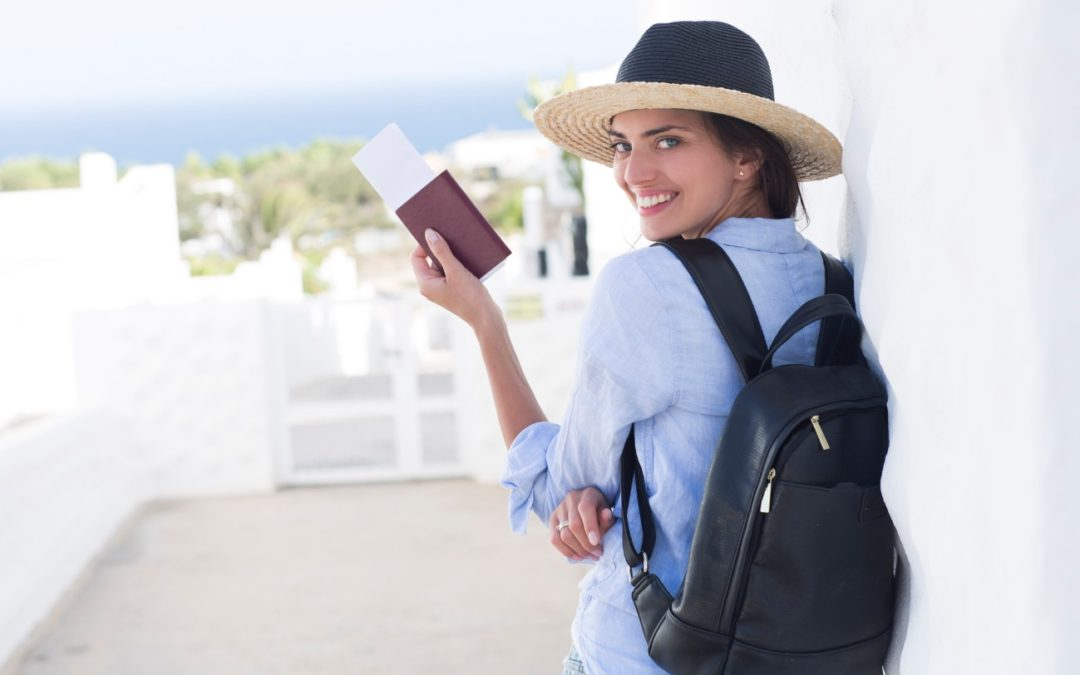 Smiling woman with a hat and a passport in her hand
