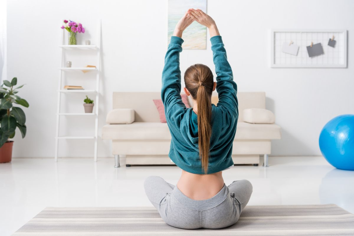 Young woman with comfy clothes doing yoga in her home