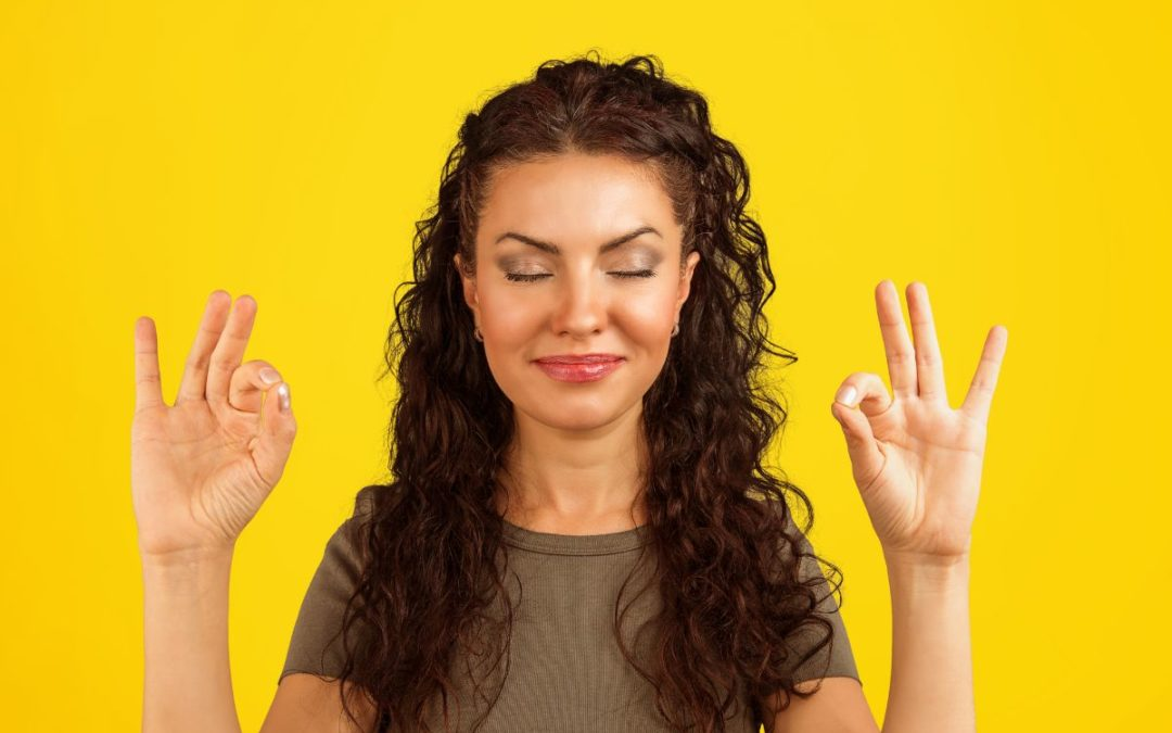 Woman smiling and doing meditative gesture (yellow background)