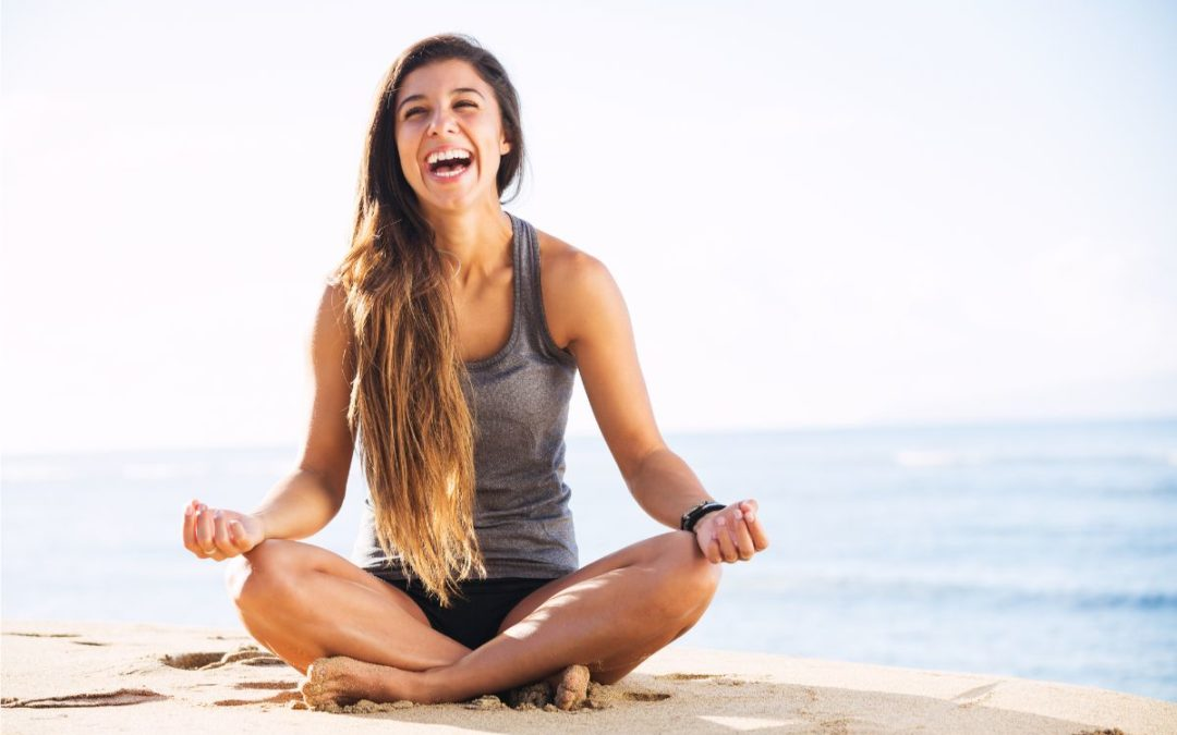 Woman laughing and meditating by the beach