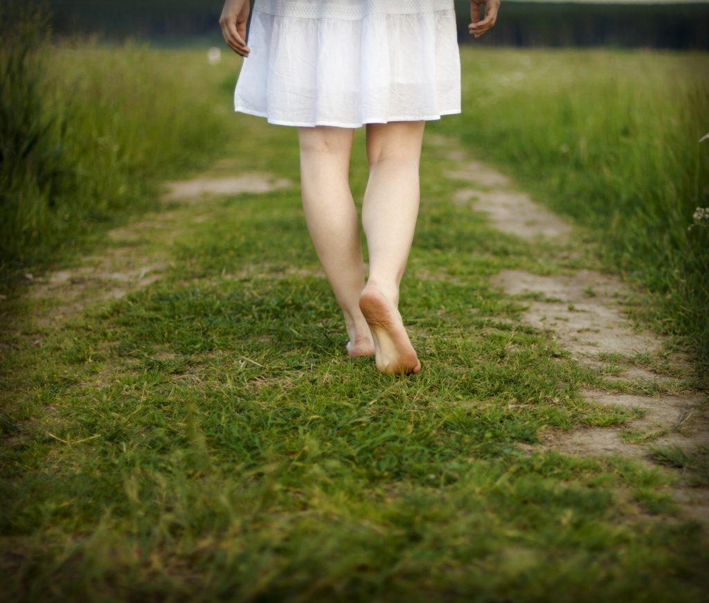 woman walking barefeet on grass path
