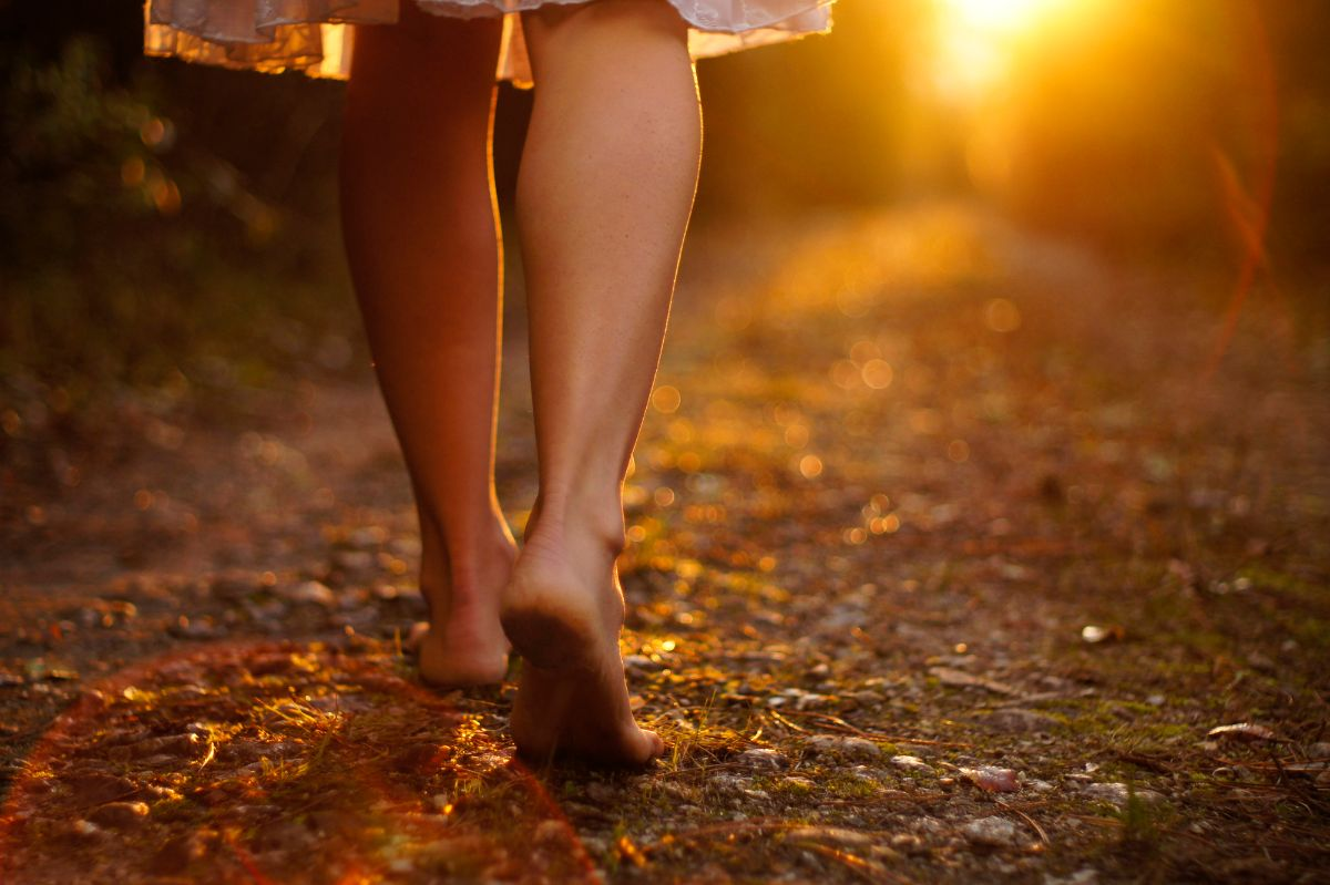 Woman walking on a dirt road with the sun setting before her