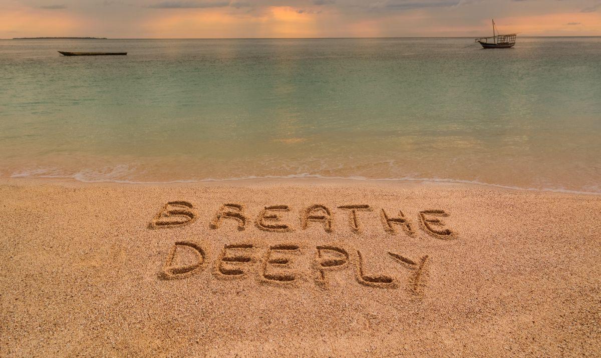 Breathe deeply written on sand