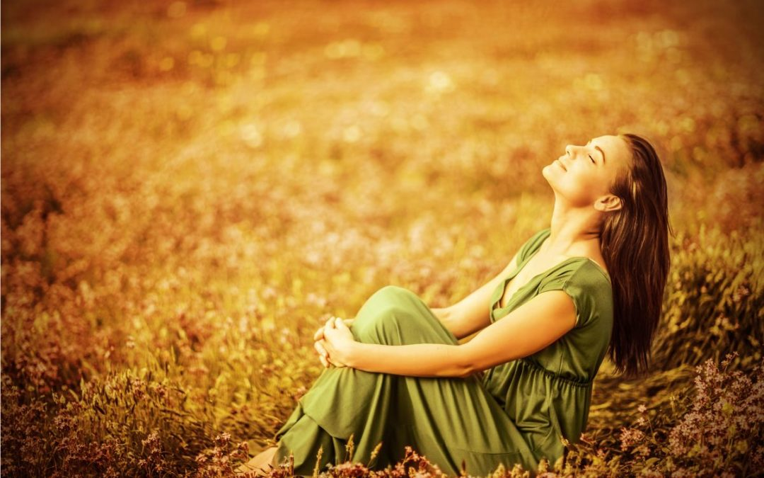 A smiling woman relaxing with eyes closed on a golden field