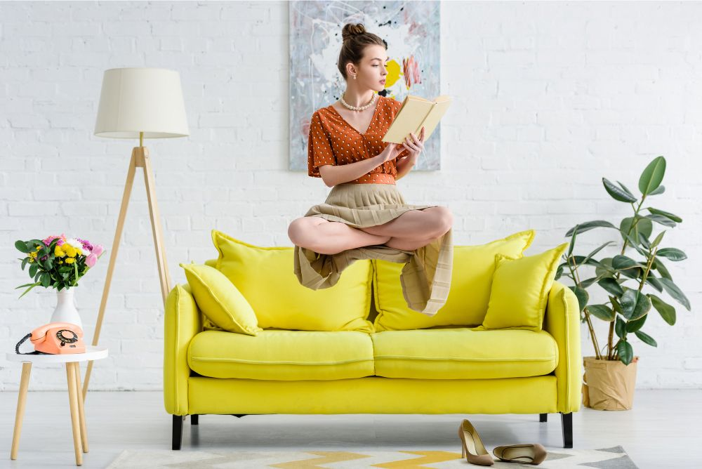 levitating woman reading book by a floor lamp