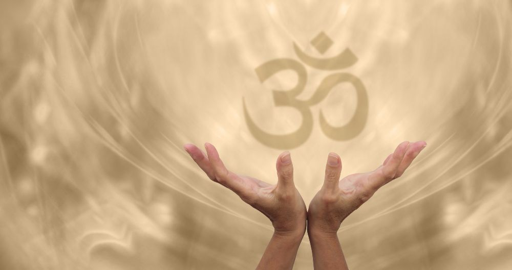 Hands of woman holding an glowing om symbol