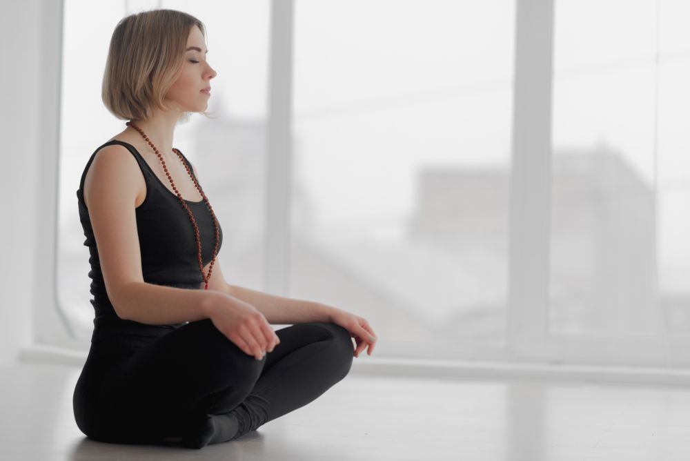 Sitting woman meditating in a white/grey room