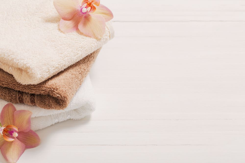 Warm towels on a bright background surrounded by orchids