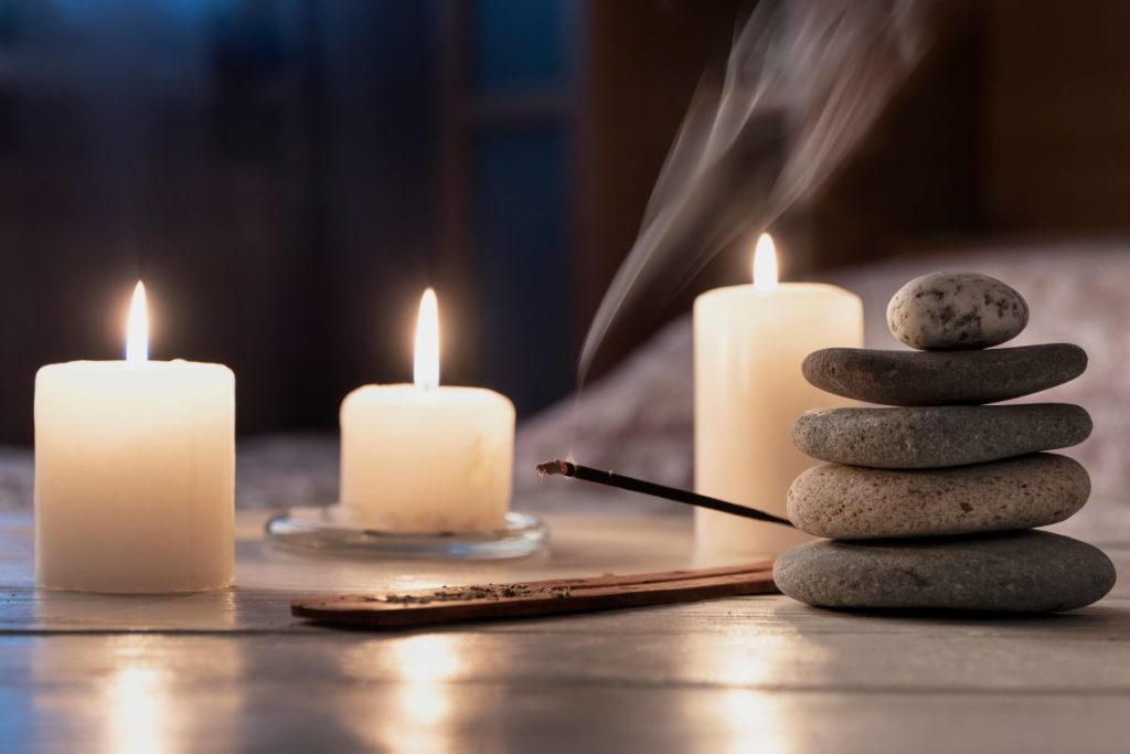Candles, incense and cairn stones on the floor in a meditative home