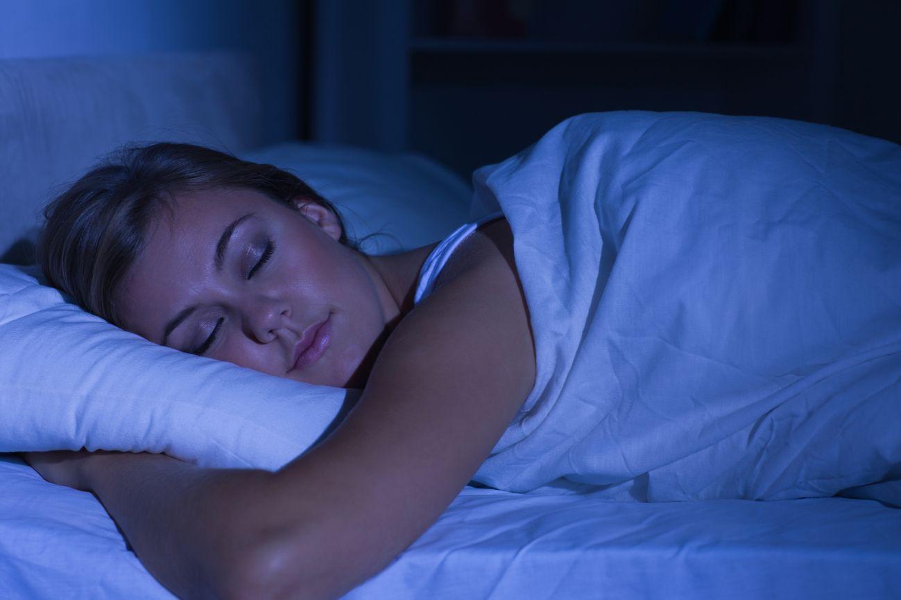 Serene woman sleeping at night in her dark bedroom