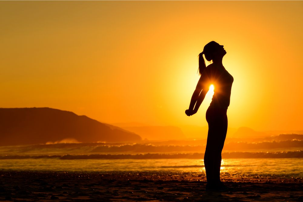 Relaxing exercises on beach at sunset