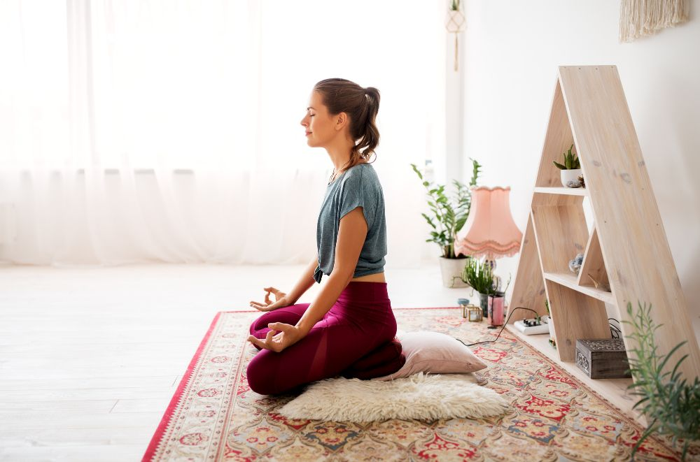 Woman meditating in a bright cozy corner in her home