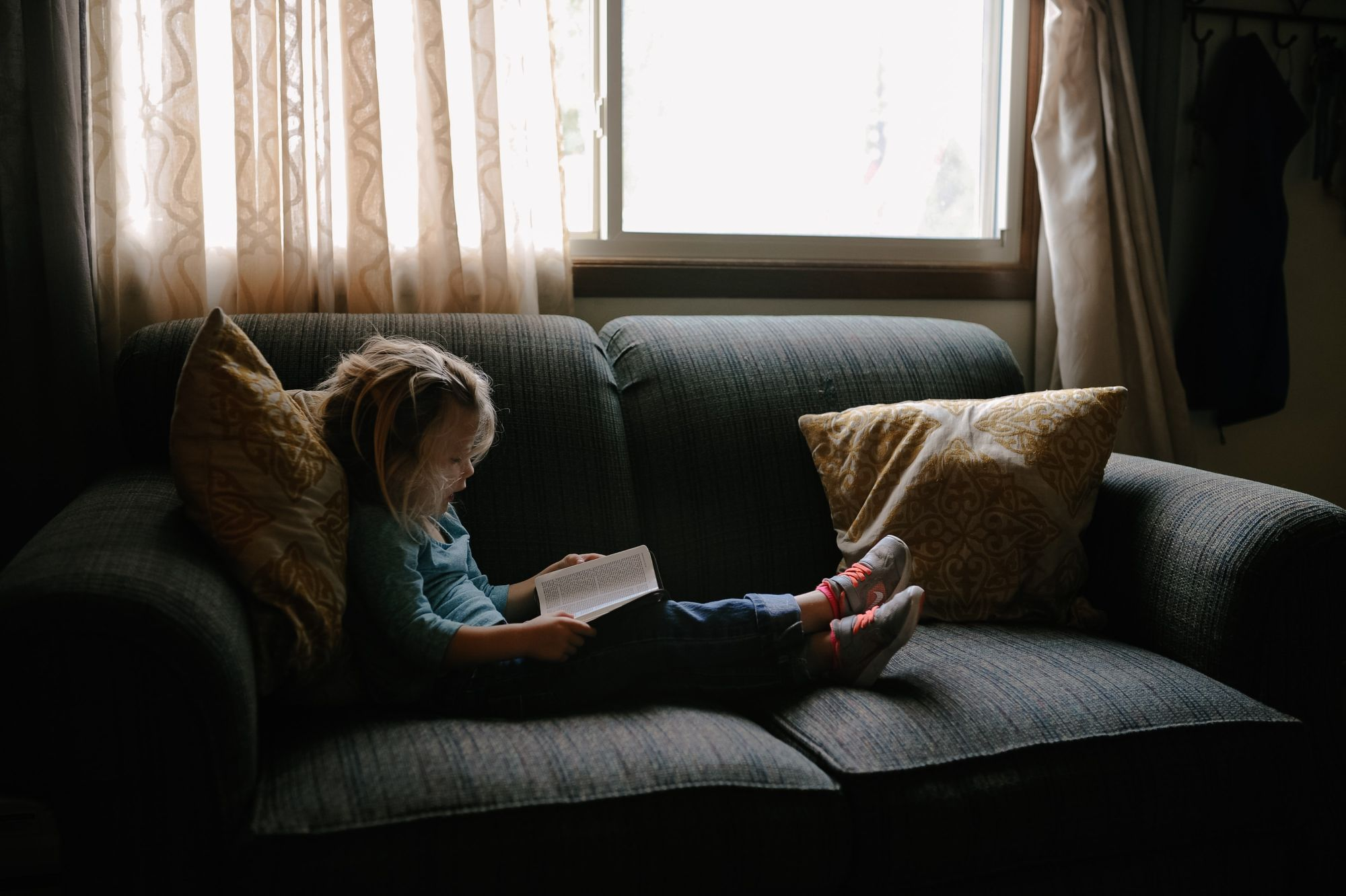 Little girl sitting on sofa reading a book