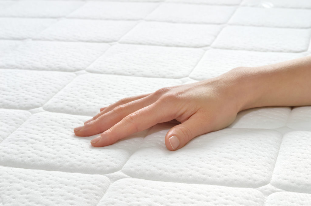 Choosing mattress and bed. Close-up of female hand touching and testing mattress in a store.