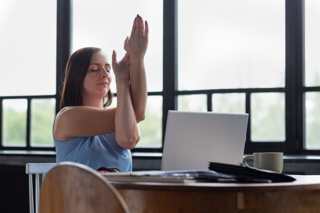 Caucasian woman at room with her crossed arms doing yoga exercise resting during working day. Garudasana, Eagle pose.