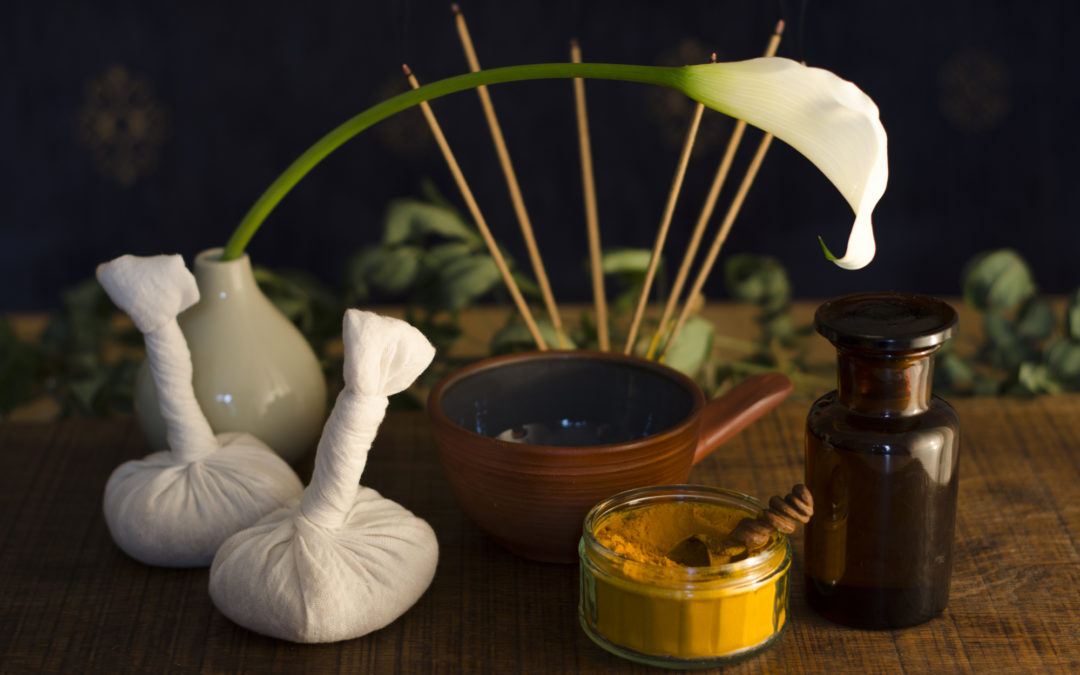 An arrangement of turmeric, spice, oil bowl and bottle, and massage poultice boluses used in Ayurveda massage, with an exotic flower and incense burning in the background.