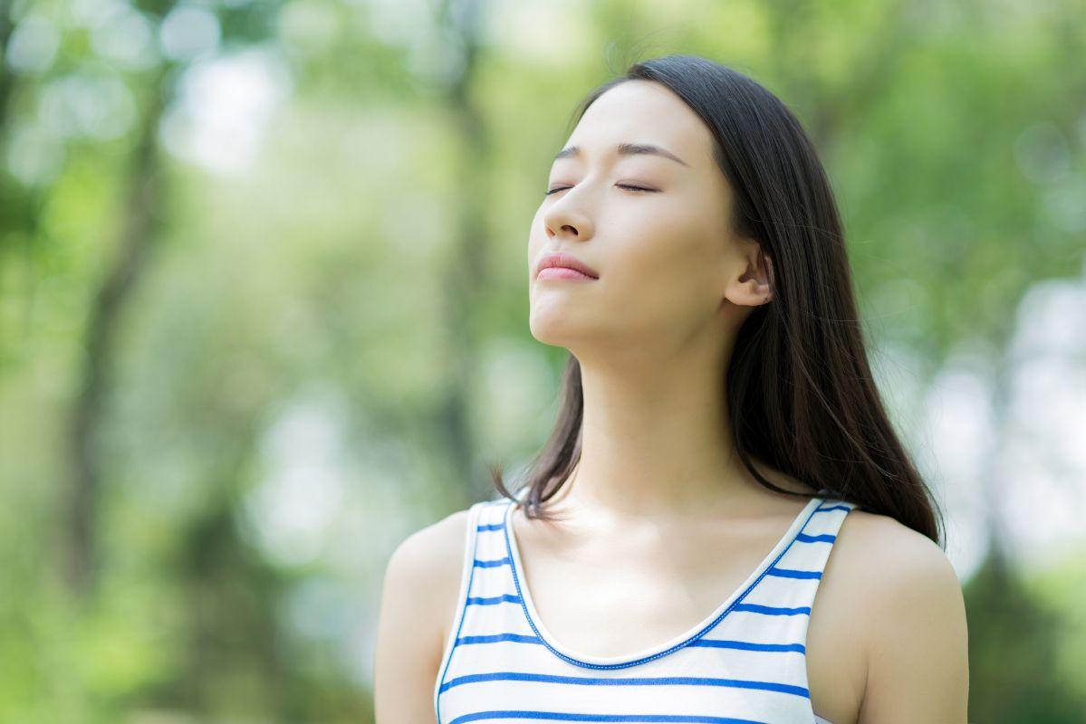 Beautiful asian woman breathing in nature