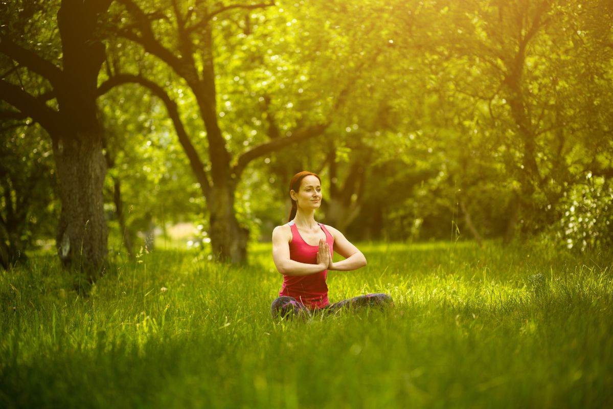 woman meditating in the green forest