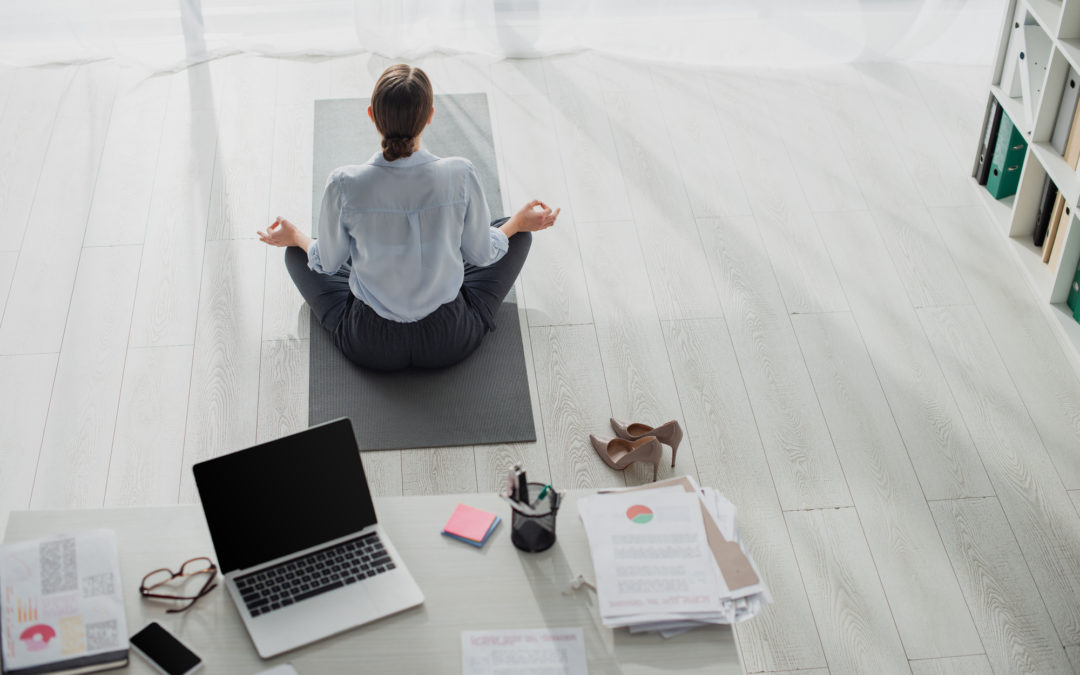 Back view of businesswoman practicing yoga in lotus position with gyan mudra on carpet in office with laptop