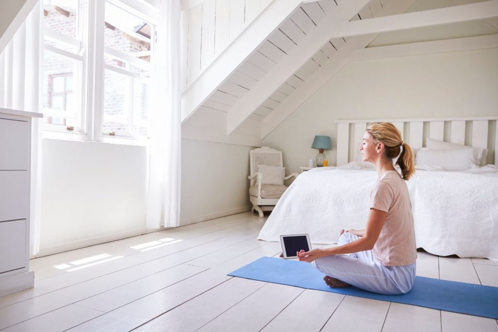 Woman meditating in a white attic with a tablet meditation app
