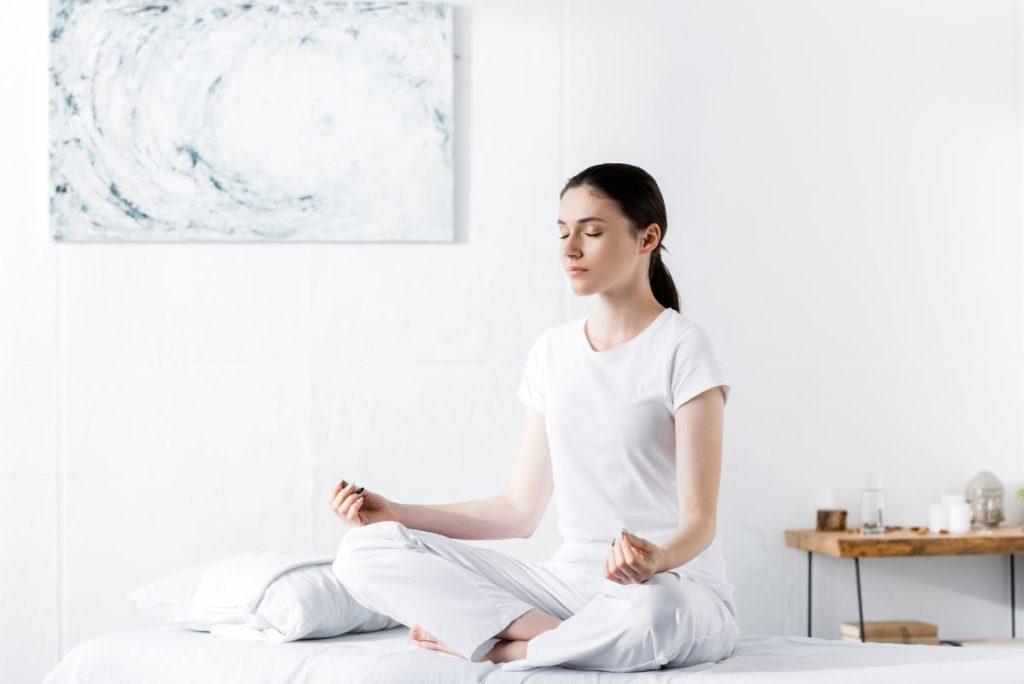 Woman meditating in her bedroom