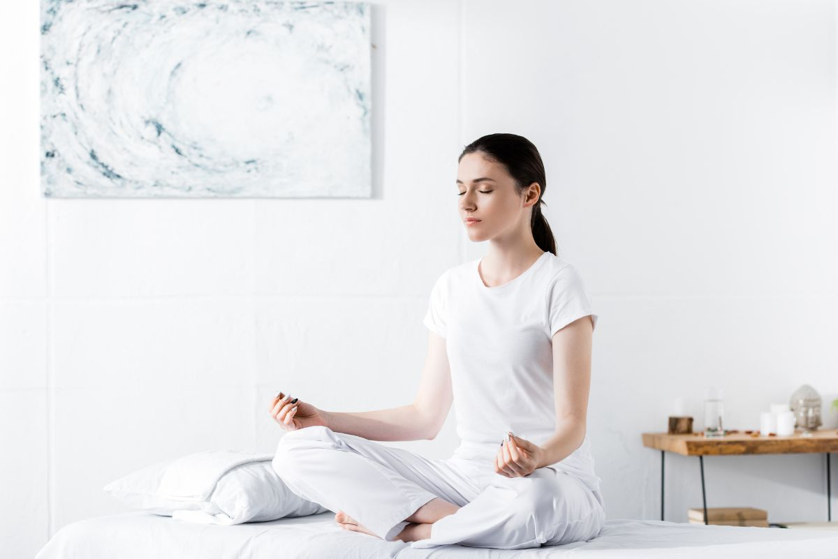 Woman meditating in her bedroom