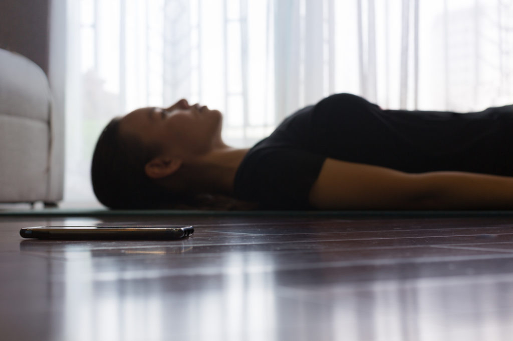 Woman on yoga mat meditating sleeping position beside her smartphone