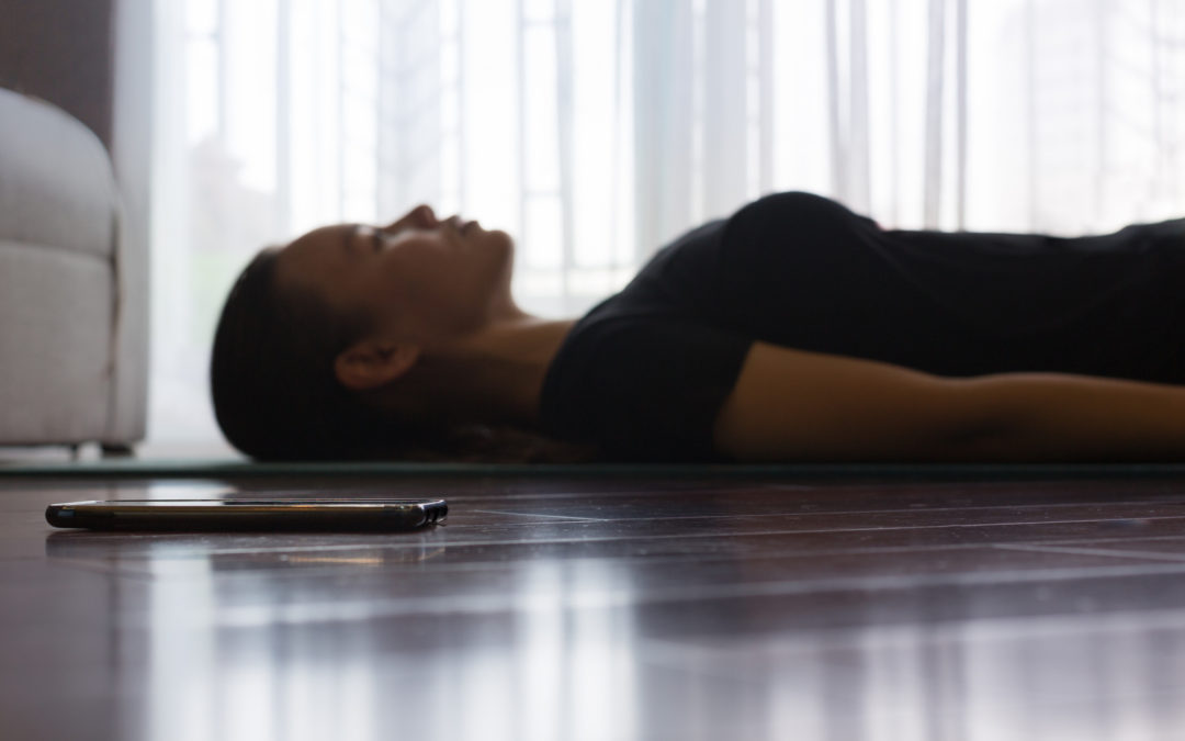 Woman on yoga mat meditating sleeping position beside her smartphone
