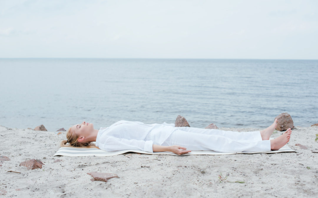 blonde woman with closed eyes meditating while lying on yoga mat near sea