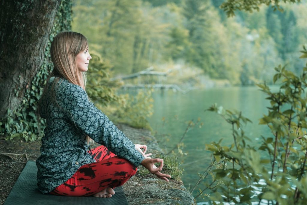 woman doing mindfulness meditation in nature