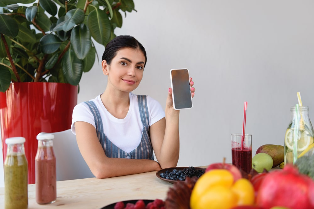 Woman showing smartphone amidst fruits and smoothies